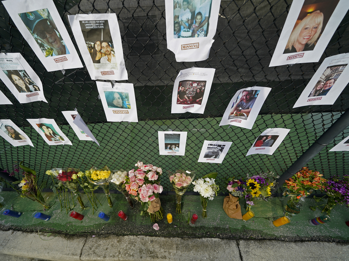 A memorial near the site holds photos of missing people in Surfside, Fla.