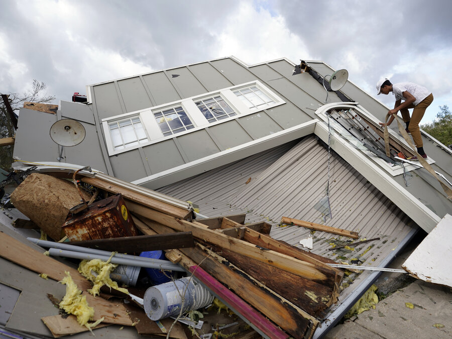 Jeremy Hodges climbs up the side of his family's destroyed storage unit on Monday, in Houma, La.