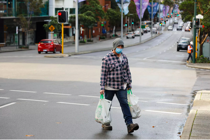 A man crosses Saint Georges Terrace, the main city thoroughfare in Perth, Australia on June 29, after several positive COVID-19 cases prompted a four-day lockdown of the Perth metropolitan area.