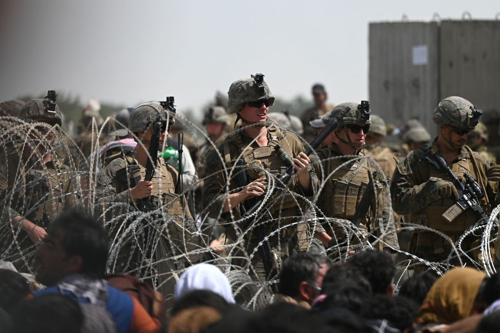 U.S. soldiers stand guard behind barbed wire in Kabul